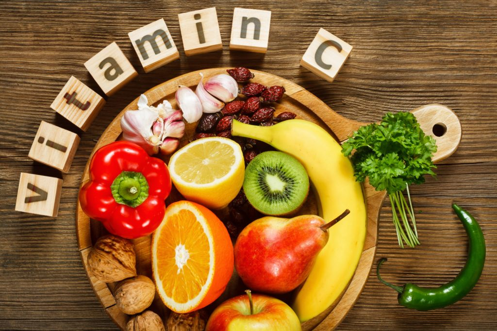 vitamin c written on the blocks and foods which are rich in vitamin c are placed in platter
